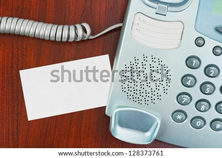 Phone and paper card on wooden table - stock photo