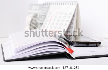 Phone and pen on a notebook - stock photo