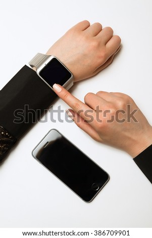 Phone and smart watch on a female hand on white background. Mock up. Top view