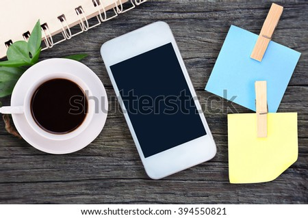 phone, blank note paper, coffee on wood desk top view. empty space for text. selective focus. - stock photo