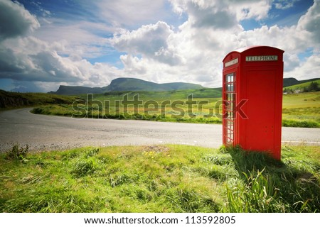 Phone booth in the middle of a green field - stock photo