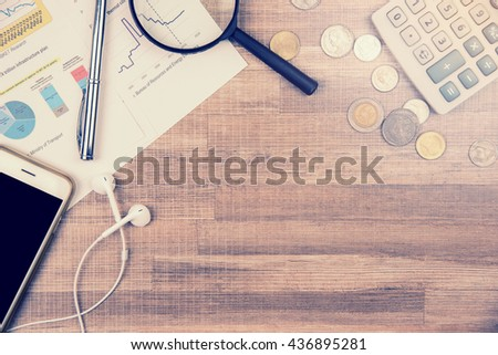 Phone, calculator, coins, magnifying glass, paper and pen on wood table, top view with copy space-financial background concept, Vintage style photo - stock photo