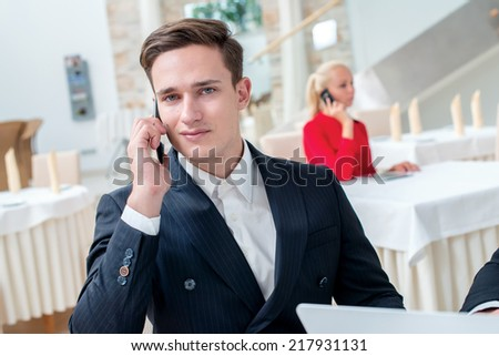 Phone call. Two successful and confident businessman sitting at the table in a business office in full costume in the office and working at a laptop and looking camera - stock photo