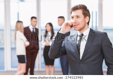 Phone call.  Young business man standing in foreground smiling and talking on the phone, his co-workers discussing business matters in the background - stock photo