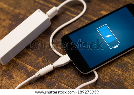 Phone charging with energy bank. Depth of field on Power bank - stock photo