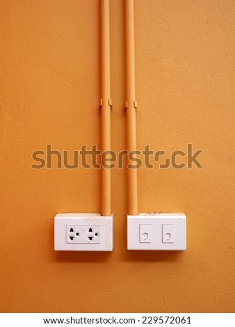Phone connector and electric plug on orange wall background - stock photo