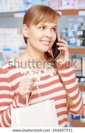 Phone consultancy. Close-up of a young smiling woman talking over the phone in a pharmacy shop  - stock photo