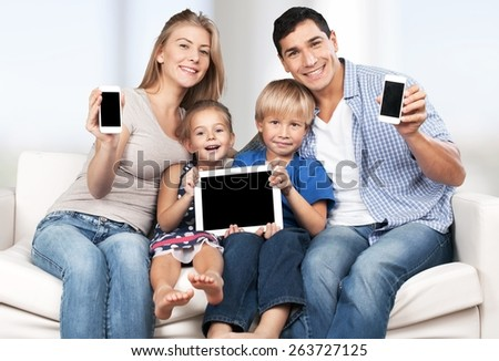 Phone. Family, child, technology and home concept - smiling parents and little girl with blank black screen smartphones at home - stock photo