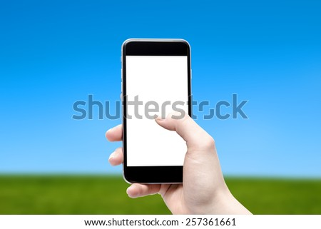 phone in hand and sky and meadow - stock photo