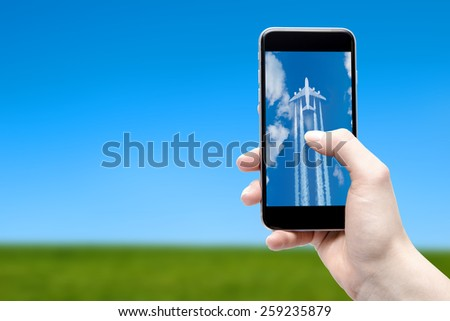 phone in hand and the plane on the screen - stock photo