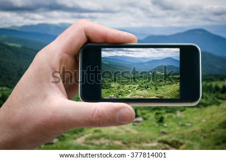 phone in hand man (photographing the landscape) photos from your phone, Self, photographing on the phone, the man photographs the mountain landscape on the phone (smartphone) side view - stock photo