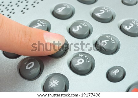 Phone keypad and woman finger, abstract communication background - stock photo