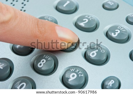 Phone keypad and woman finger - abstract communication background - stock photo