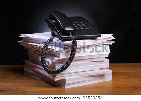 Phone lies on the big pile of a paper