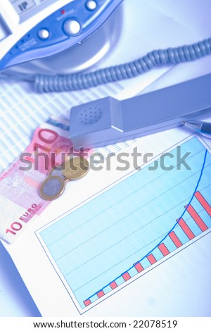 Phone, money,charts, pen and numbers representing finance. Blue tint.