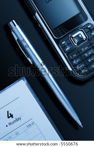 Phone, pen and notebook on a table - stock photo