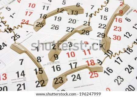 Phone Receivers on Calendar Pages - stock photo