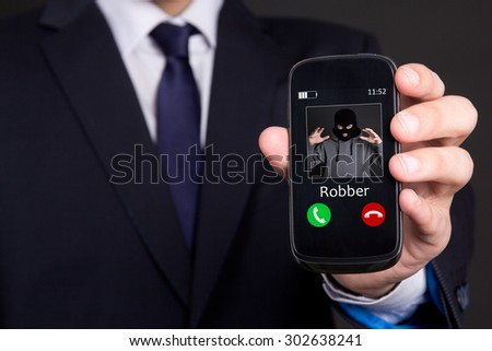 phone robbery concept - business man hand holding smart phone with incoming call from robber - stock photo