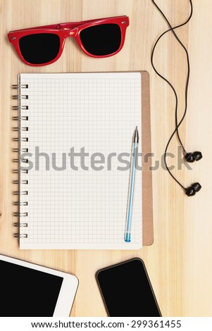 phone, tablet, notebook, headphones and sunglasses on wooden table - stock photo