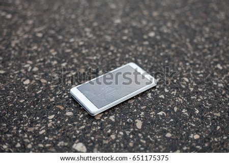 Phone with broken screen lying on the street