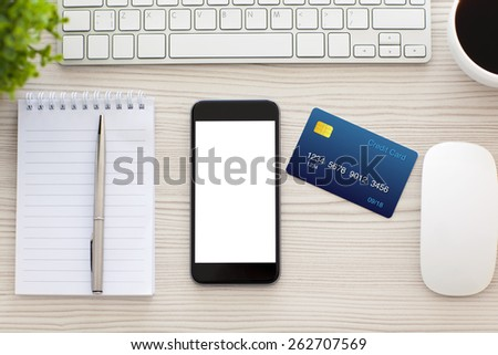 phone with isolated screen and a credit card on the table in the office - stock photo
