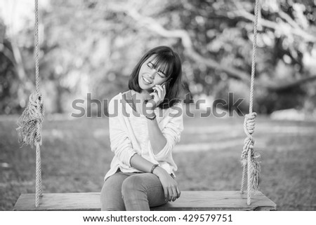 Phone woman  in talking in smart phone in park , black and white.