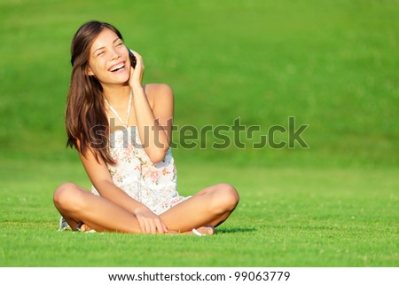 Phone woman laughing in talking in smart phone in park during spring / summer. Happy smiling beautiful young woman sitting in grass. Multiracial Caucasian / Chinese Asian female model outside in dress - stock photo