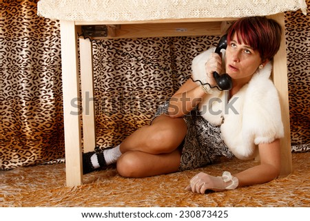 Phoning terrified woman hiding under the table