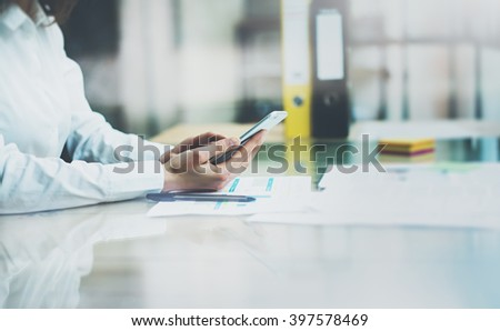 Photo account manager working new startup project modern office.Contemporary smartphone holding female hands and touching screen. Analyze statistics .Horizontal, film effect. Blurred background