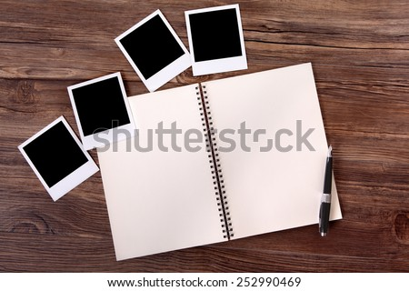 Photo album with blank polaroid style instant photo prints.  Space for copy.  - stock photo