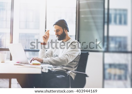 Photo bearded copywriter working with new project modern loft. Using contemprary notebook on wood table. Thinking idea. Freelance world. Blurred background, film effect, horizontal