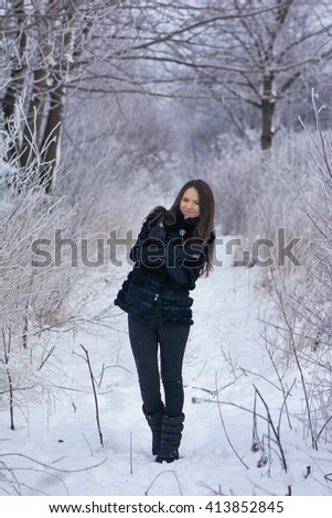 Photo beautiful smiling girl in winter park. Trees covered with frost and snow.
