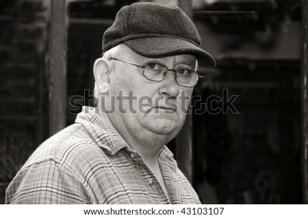 photo black and white portrait of an older senior male glasses and cap - stock photo