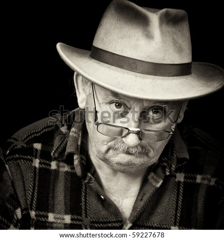 photo black and white portrait  of senior old elderly pensioner man male with sad depressed grumpy close up face portrait wearing fedora hat.