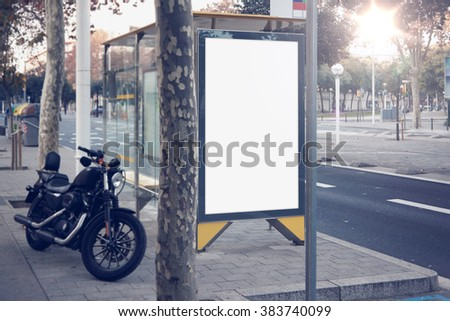 Photo blank lightbox on bus stop in the modern city. Authentic motobike parking close. Horizontal mockup, sunlight - stock photo