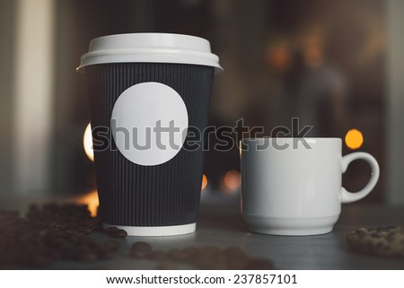 Photo blank paper cup and mugs in a coffee shop to apply logo - stock photo