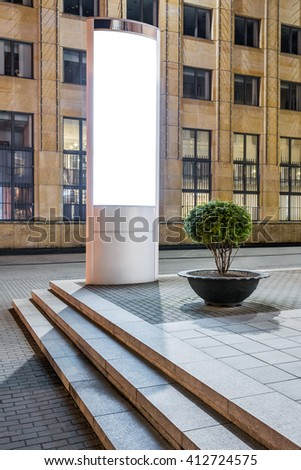 Photo blank vertical mockup of lightbox stand glowing at night in city square - stock photo