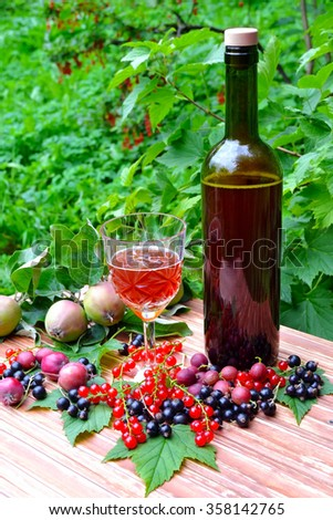 Photo bottle of red sparkling wine with a glass and berries on the table - stock photo