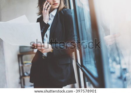 Photo business woman wearing suit, talking smartphone and holding papers in hands. Open space loft office. Panoramic windows background. Horizontal mockup. Film effect - stock photo