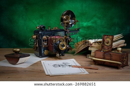 Photo camera and drawing on a wooden table. Style Steampunk.