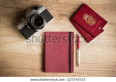 Photo camera and passport on wooden desk - stock photo