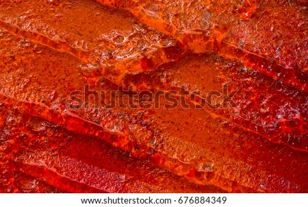 Photo close up of abstract art glass of red color similar to fruit jelly. Glass abstract background. Pattern. Glass abstract. Modern Art  deco. Decor glass.