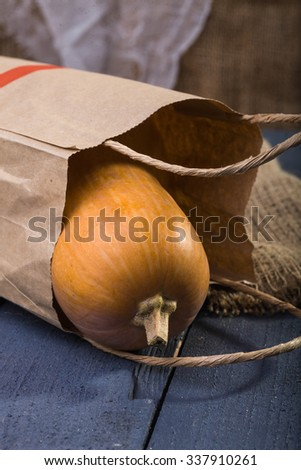 Photo closeup autumn still life one big whole fresh orange pumpkin gourd lying in paper packet near sackcloth coarse fabric on blue wooden table over rustic background, vertical picture  - stock photo