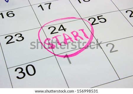 "Photo closeup of dates on calendar page with pink marker inscription ""start"" - stock photo"