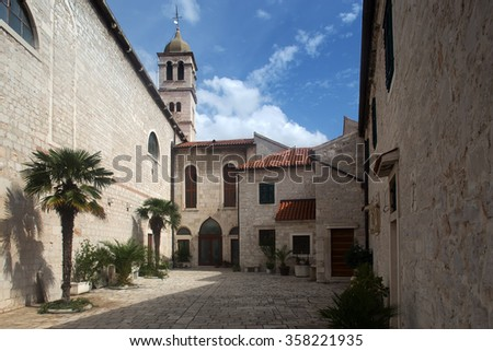 Photo closeup of medieval inner yard old white stone church against blue sky day time on townscape background, horizontal picture - stock photo