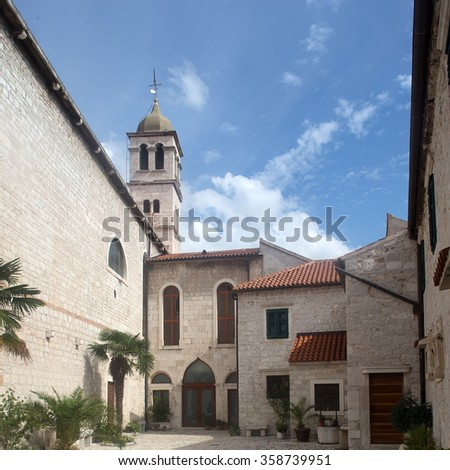 Photo closeup of medieval inner yard old white stone church against blue sky day time on townscape background, square picture - stock photo