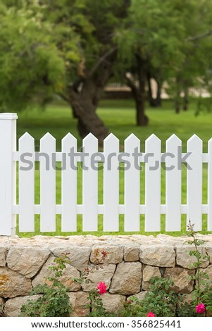 Photo closeup of white wooden palisade fence on stone basement with rose bushes outside on summer day on green landscape background, vertical picture  - stock photo
