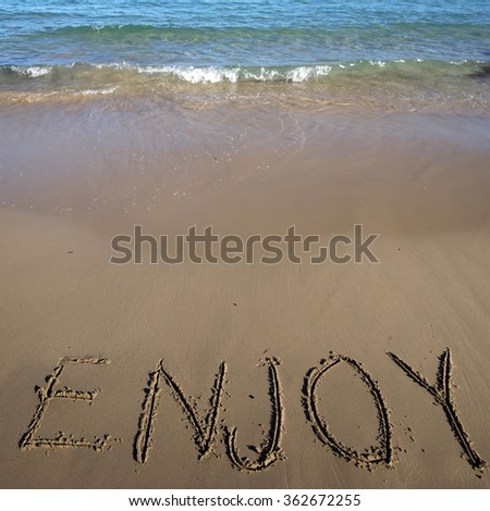 Photo closeup of word enjoy written on beautiful wet beige beach sea marine grained sand against blue waves with splashes white spindrifts running on seashore on seascape background, square picture - stock photo