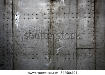 Photo closeup old rusty grunge steel aluminum fragment of protective structure made of metal plates sheets assembled with button head rivets on armor textured background, horizontal picture  - stock photo