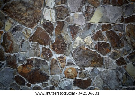 Photo closeup outdoor of brown gray stone wall facade exterior of rocks of various sizes and forms on seamless mural background, horizontal picture  - stock photo